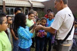 Students are taught how to safely handle birds that live in the schoolyard.